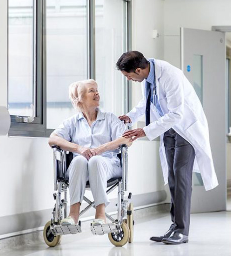 Physician is talk with a woman sitting at wheelchair